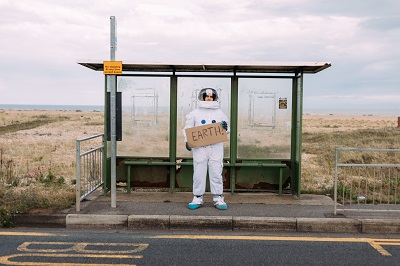 Picture of a spaceman waiting at a bus stop holding a cardboard sign that says Earth